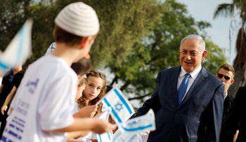 Israeli Prime Minister Benjamin Netanyahu, right, greets students as they wave Israeli flags during a ceremony opening the school year in the Jewish settlement of Elkana in the Israeli-occupied West Bank Sunday, Sep. 1, 2019