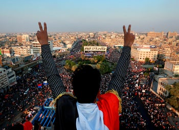 A protester flashes the victory sign while anti-government protesters gather in Tahrir Square during ongoing protests in Baghdad, Iraq, Thursday, Oct. 31, 2019.