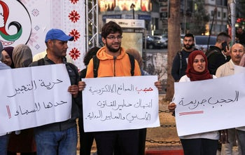 Palestinian journalists lift placards supporting freedom of expression during a rally in the West Bank city of Ramallah, October 23, 2019.