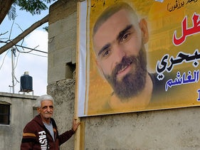 Majid Bakhri next to a memorial poster for his son Raad, in Kafr Zibad this week.