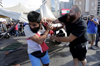 A Hezbollah supporter, right, fights with an anti-government protester during clashes erupted between them during ongoing protests against the Lebanese government in Beirut, Lebanon, October 29, 2019