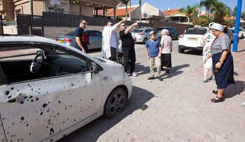 Residents inspect damage caused by rocket shrapnel in the southern town of Sderot, November 2, 2019,