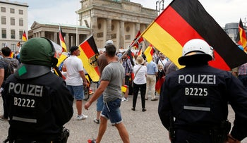 Supporters of German AfD wave flags in front of the Brandenburg Gate in Berlin, Germany, Sunday, May 27, 2018.