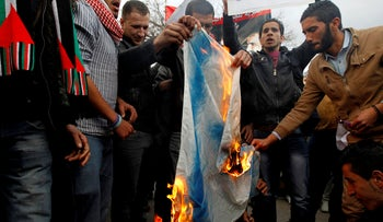 Jordanian demonstrators burn an Israeli flag during a protest against the shooting of a Palestinian judge from Jordan by Israeli soldiers. Amman, March 11, 2014