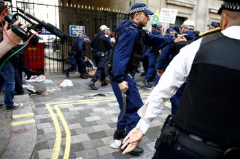 A police officer holds a blade recovered from pro-Pakistan demonstrators during a protest outside the Indian High Commission against India's change to Kashmir's constitutional status in Kashmir. London, August 15, 2019
