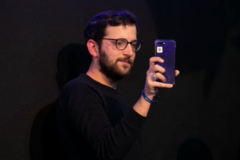 Jonatan Urich uses his phone to film at a Likud conference, June 29, 2019.
