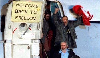 David Roeder,who was among 52 Americans held hostage in Iran for 444 days, shouts and waves as he arrives at Rhein-Main U.S. Air Force base in Frankfurt from Algeria on January 21, 1981.