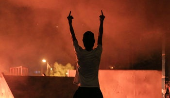 An Iraqi protester gestures with his fingers during an anti-government demonstration in the Shiite shrine city of Karbala, south of Iraq's capital Baghdad on October 27, 2019.