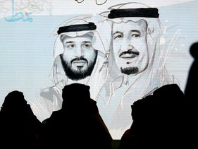 Saudi participants at the Future Investment Initiative stand to greet the national anthem in front of a screen displaying images of Saudi King Salman and Crown Prince Mohammed bin Salman in Riyadh, October 28, 2019.