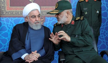 Iranian President Hasan Rohani, left, listens to the chief of the Revolutionary Guard, Gen. Hossein Salami, at a military parade outside Tehran, September 22, 2019.