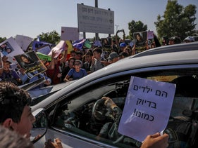 Children protest the detention of their classmate outside Givon prison, Ramla, October 31, 2019. The sign says: 'They're kids just like us!'