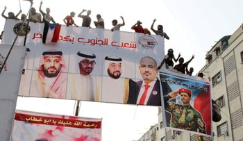 Supporters of Yemen's separatists stand on a billboard during a rally to show support to the United Arab Emirates amid a standoff with the Saudi-backed government, in Aden, Yemen, September 5, 2019.