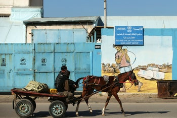 A Palestinian man rides his horse past an UNRWA office in Gaza City, January 8, 2018