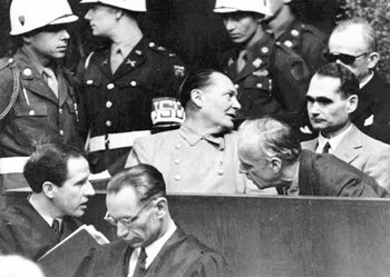 Nazi German Foreign Minister Joachim von Ribbentrop, right, leans in front of Rudolf Hess, Hitler's deputy, to confer with his lawyer, lower left, during the Nueremberg trial, on March 27, 1946.