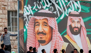 Football fans stand beneath a large banner depicting Saudi King Salman bin Abdulaziz and his son Crown Prince Mohammed bin Salman as they attend the World Cup 2022 Asian qualifying match between Palestine and Saudi Arabia in the West Bank, October 2019.