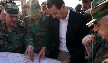 Syrian President Bashar al-Assad shown in handout picture from October 21, 2019 looking at a map with army officers on the edges of Idlib province.