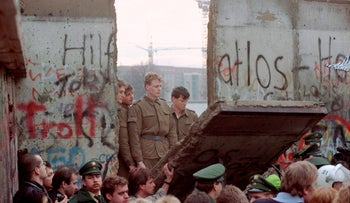 East German border guards are seen through a gap in the Berlin wall after demonstrators pulled down a segment of the wall at Brandenburg gate, Berlin, November 11, 1989.
