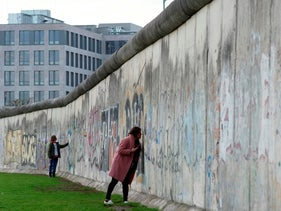 People touching remains of the Berlin Wall on the city's Bernauer Strasse, November 8, 2019.
