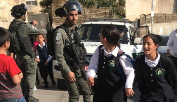 Palestinian girls walk by Israeli police officers in the Palestinian East Jerusalem neighborhood of Isawiyah, on Friday, November 8, 2019.