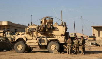 U.S. Army soldiers stand outside their armored vehicle on a joint base with Iraqi army south of Mosul, Iraq, on February 23, 2017.