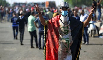 An Iraqi protester, draped in a national flag, flashes the victory sign near the capital Baghdad's Al-Jumhuriyah Bridge on October 26, 2019.