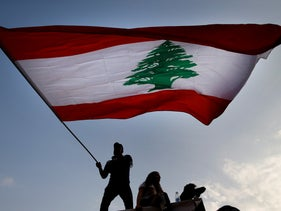 A protester waves the Lebanese flag during ongoing protests against the government, in front of the government palace in Beirut, Lebanon Nov. 9, 2019