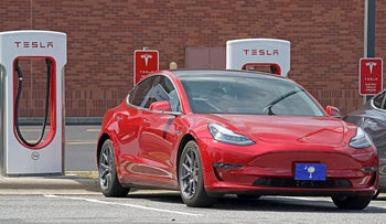 This Friday, July 19, 2019, file photo shows a Tesla vehicle charging at a Tesla Supercharger site in Charlotte, N.C. Tesla's electric car sales accelerated again during the summer, but the company is still lagging behind the pace it needs to reach CEO Elon Musk's goal for the entire year