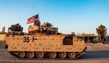 A U.S. Bradley armored personnel carrier drives near the town of Tal Tamr in the northeastern Syrian Hasakeh province November 10, 2019