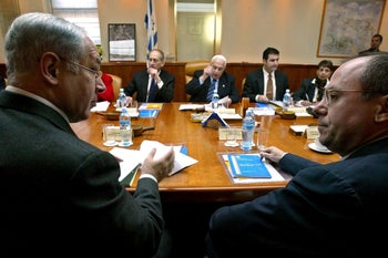 Then finance minister Netanyahu looks at then foreign minister Silvan Shalom, as PM Ariel Sharon opens a cabinet meeting, Jerusalem, March 19, 2006