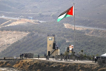 King Abdullah II of Jordan standing to attention with army troops under a Jordanian national flag during a ceremony at the Jordan Valley site of Naharayim, also known as Baqura, east of the Jordan River on November 11, 2019.