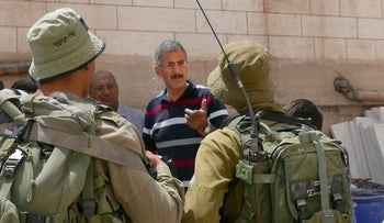 Israeli soldiers from the Nahal Battalion talking to a Palestinian in Hebron, West Bank.