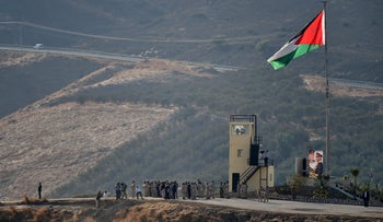 King Abdullah II of Jordan standing to attention with army troops under a Jordanian national flag during a ceremony at the Jordan Valley site of Naharayim on November 11, 2019.
