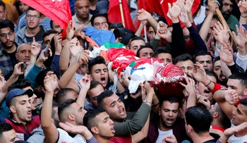Mourners carry the body of Omar al-Badawi during his funeral in al-Arroub refugee camp in the West Bank, November 11, 2019.