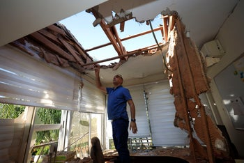 A man looks at the damage to a house in Sderot, Israel, after it was hit by a rocket fired from Gaza Strip, November 12, 2019.