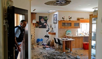 An Israeli policeman inspects the damage inside a house in the southern Israeli town of Netivot, November 12, 2019.
