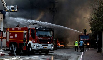 Firefighters deploy after a factory hit by a rocket caught fire in Sderot, southern Israel , Israel, November 12, 2019.