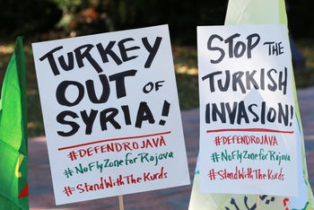 A small group of protesters post signs for a rally against Turkish President Recep Tayyip Erdogan in front of the White House in Wednesday, November 13, 2019