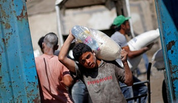 A Palestinian carries food supplies at an aid distribution center run by the United Nations Relief and Works Agency (UNRWA), in Al-Shati refugee camp in Gaza City September 25, 2019