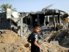 A Palestinian boy looks on as he stands in front of the remains of a house destroyed in an Israeli air strike in the southern Gaza Strip November 13, 2019.