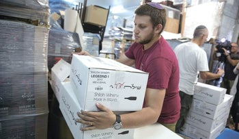 A worker carrying boxes containing wine bottles for export at Shiloh Wineries, north of the West Bank city of Ramallah, in 2015.