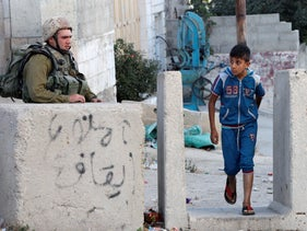 An Israeli soldier blocks an entrance to the Jewish settlers' zone of Hebron's Tel Rumeida neighborhood,near Shuhada Street in the West Bank city's center. September 18, 2016