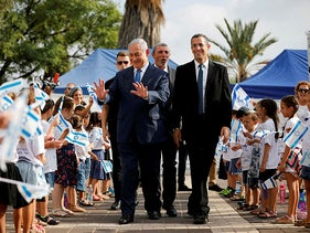 Israeli Prime Minister Benjamin Netanyahu walks with Education minister Rafi Peretz as he greets students during a ceremony opening the school year in the Jewish settlement of Elkana in the Israeli-occupied West Bank September 1, 2019.