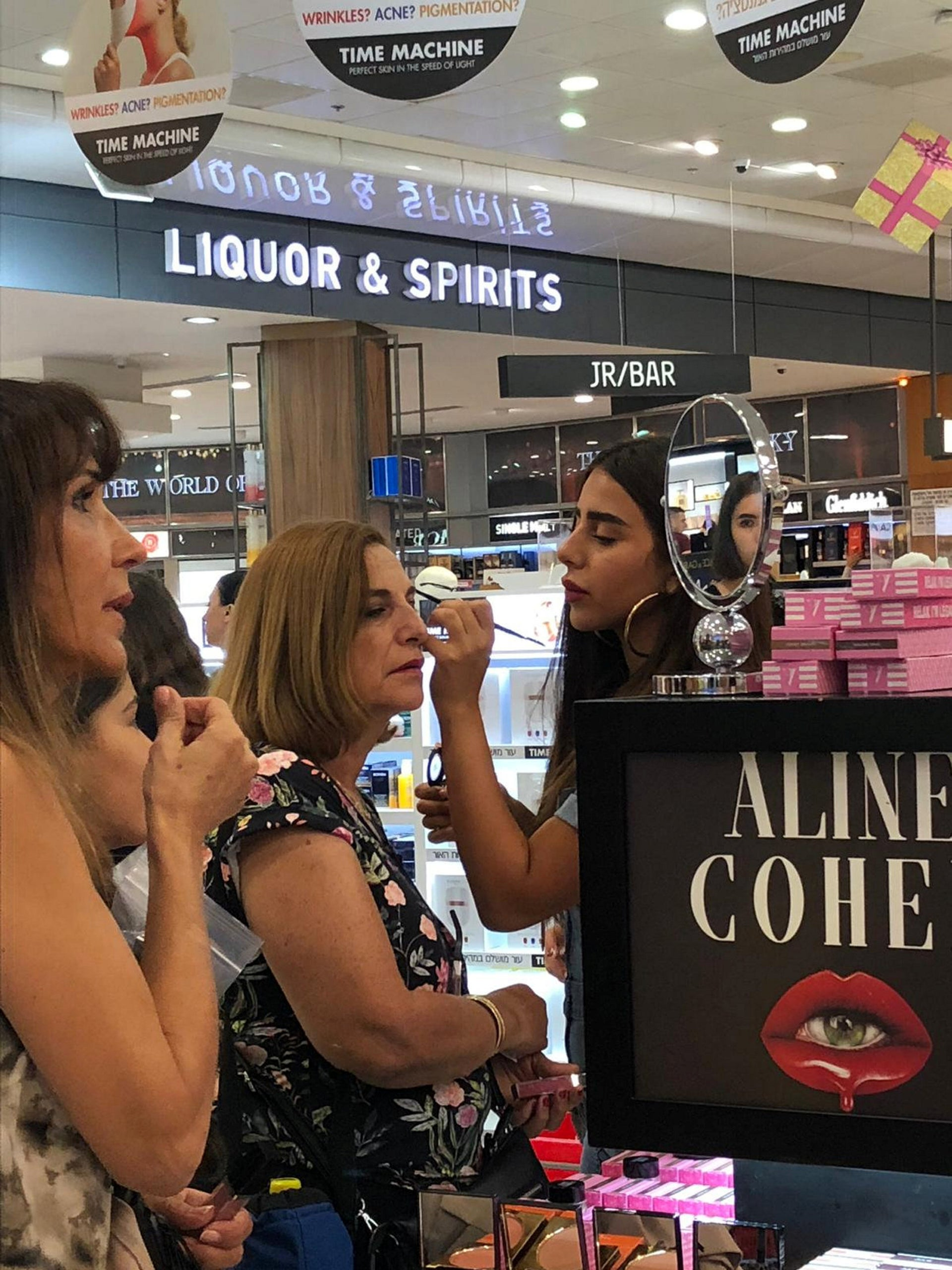 An eclectic crowd of women gathers around, pushing aside the salesgirls working for competing brands. They hold up their smartphones, trying to capture the scene as Cohen paints eyebrows on a 60-year-old woman in a flowery shirt and sports shoes.
