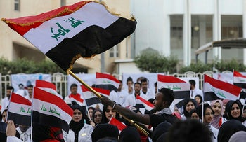 Iraqi medical students wave national flags as they take part in an anti-government protest amid ongoing student strikes at the campus of the university of Basra, in the  southern city of the same name, on November 14, 2019.