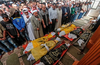 Palestinians attend the funeral procession of members of the same family who were killed overnight in an Israeli airstrike, on November 14, 2019 in Deir al-Balah.