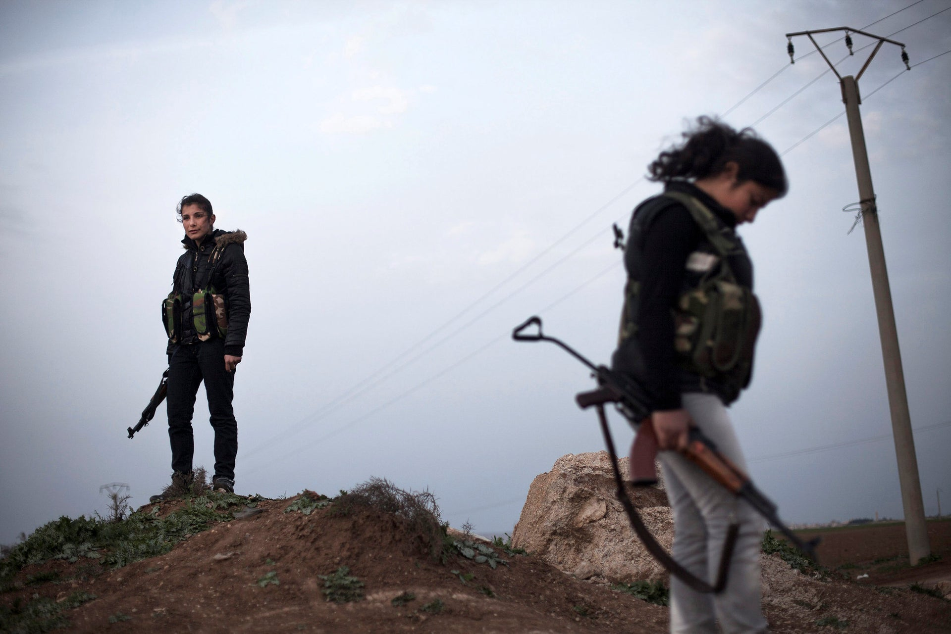 Kurdish female members of the Popular Protection Units stand guard at a check point near the northeastern city of Qamishli, Syria, 2013.