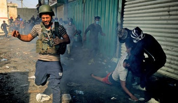 An Iraqi protester runs as others help an injured person amidst clashes at the capital Baghdad's Khallani square on November 15, 2019.