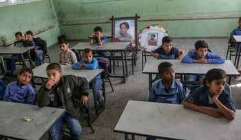 Palestinian pupils sit in class where commemorative pictures of their late classmate Muath are displayed, at his school in Dir al-Balah, November 16, 2019.