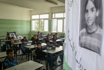 Palestinian pupils sit in class in front of a commemorative picture of their late classmate Muath at his school in Dir al-Balah, November 16, 2019.