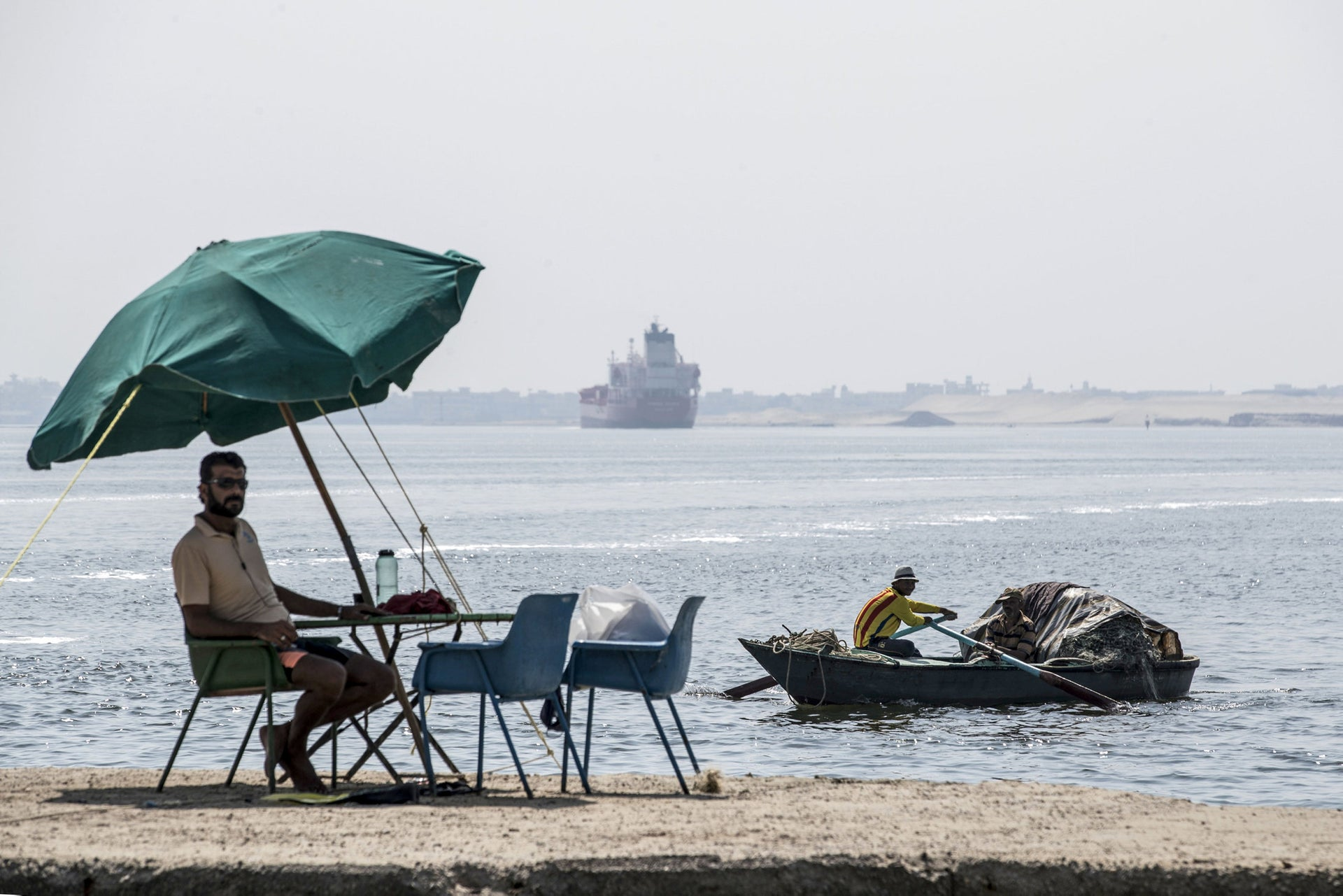 A fisherman takes a rest as a cargo ship sails through the Suez Canal in the Egyptian port city of Ismailia, October 14, 2019.